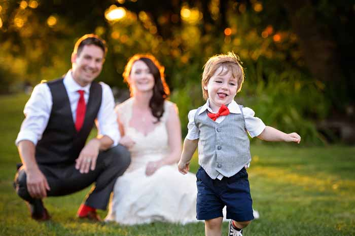 The couple in the background while their son, the ring bearer, runs towards the camera laughing at Stonefields