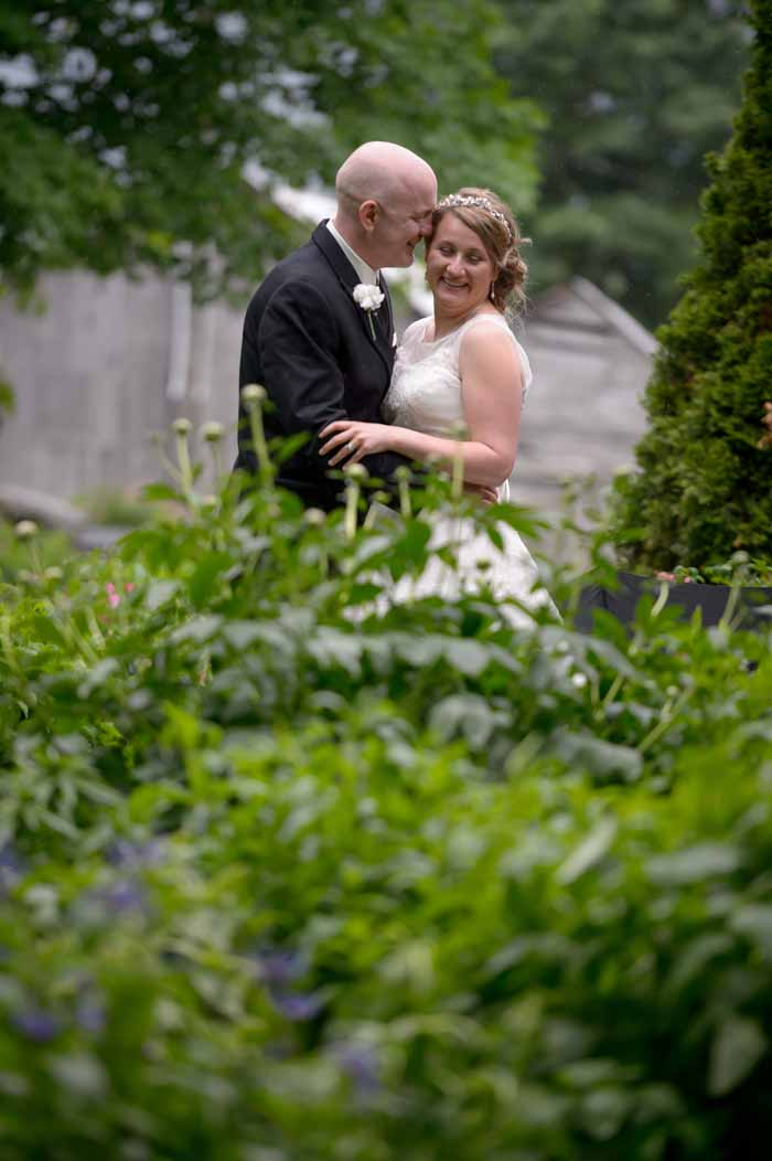 Couple embracing in the rain at their wedding at Stanleys Old Maple farm